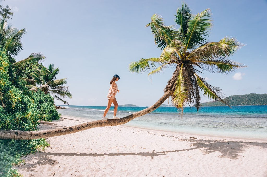 A girl walking on the palm in Seychelles