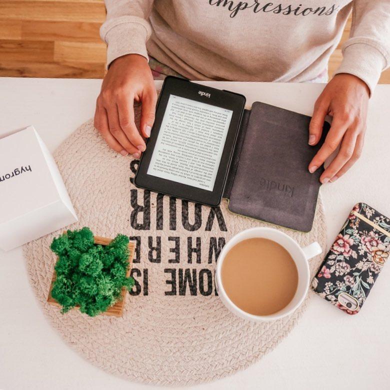 flatlay dziewczyna czytająca książkę na kindle, telefon z obudową Richmond Finch i Borcaseu hygrometr
