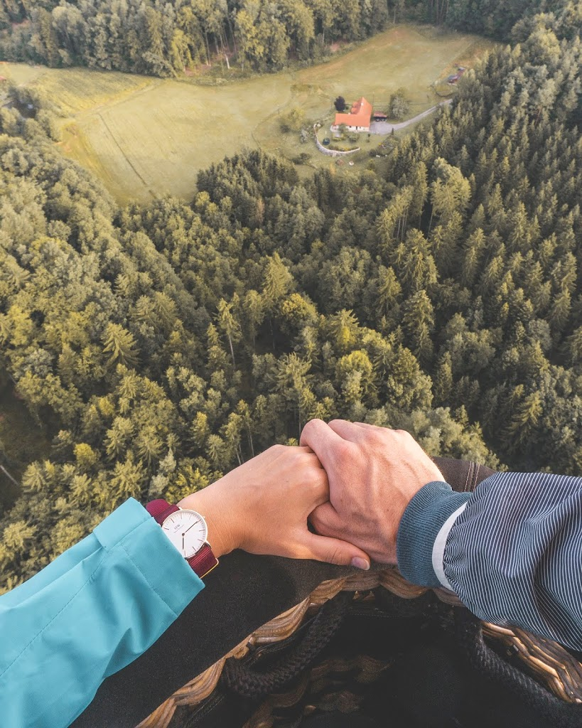holding hands with the Daniel Wellington watch, view from the hot air balloon flight in Styria Austria