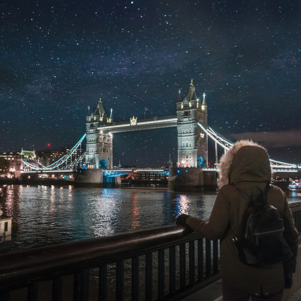 Tower Bridge in London by night. Girl standing in front of the camera watching the sky full of stars.