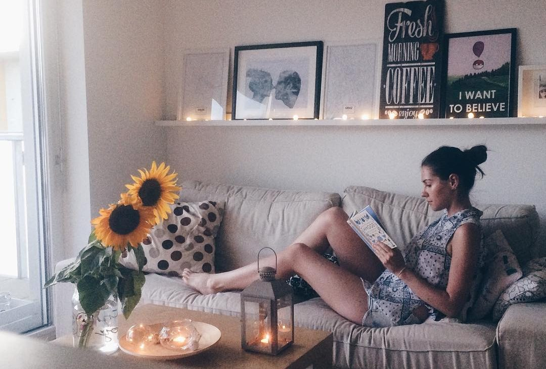 girl reading a book on the couch lifestyle blog