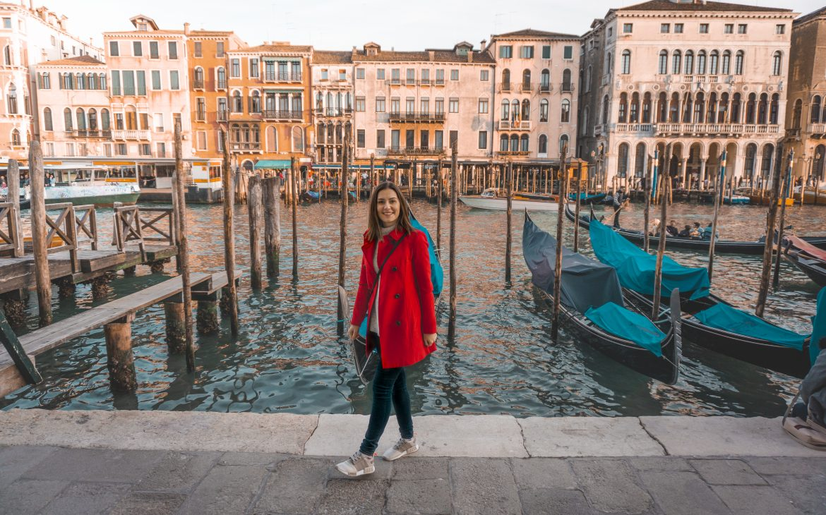 A girl in the red coat smiling and standing in front of the Venice canal.