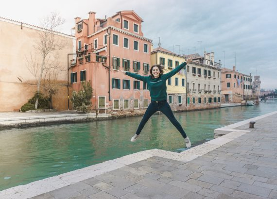 Girl jumping near the canal in Venice.