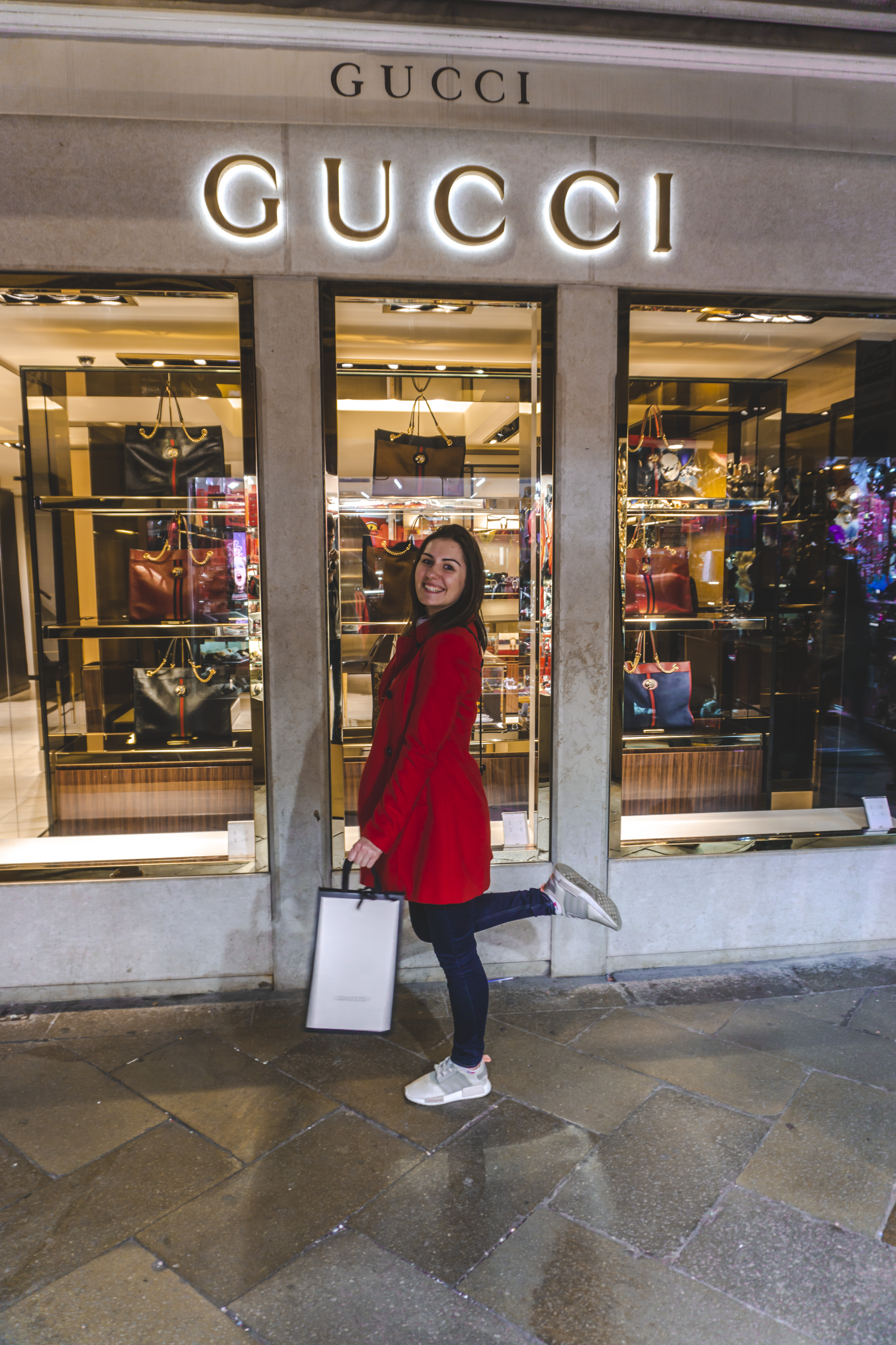 Girl in the red coat smiling after shopping in Gucci and holding a white bag.