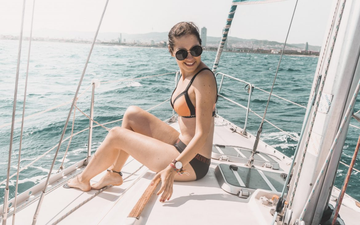 A girl with black sunglasses, sitting on the sailing boat in Barcelona.