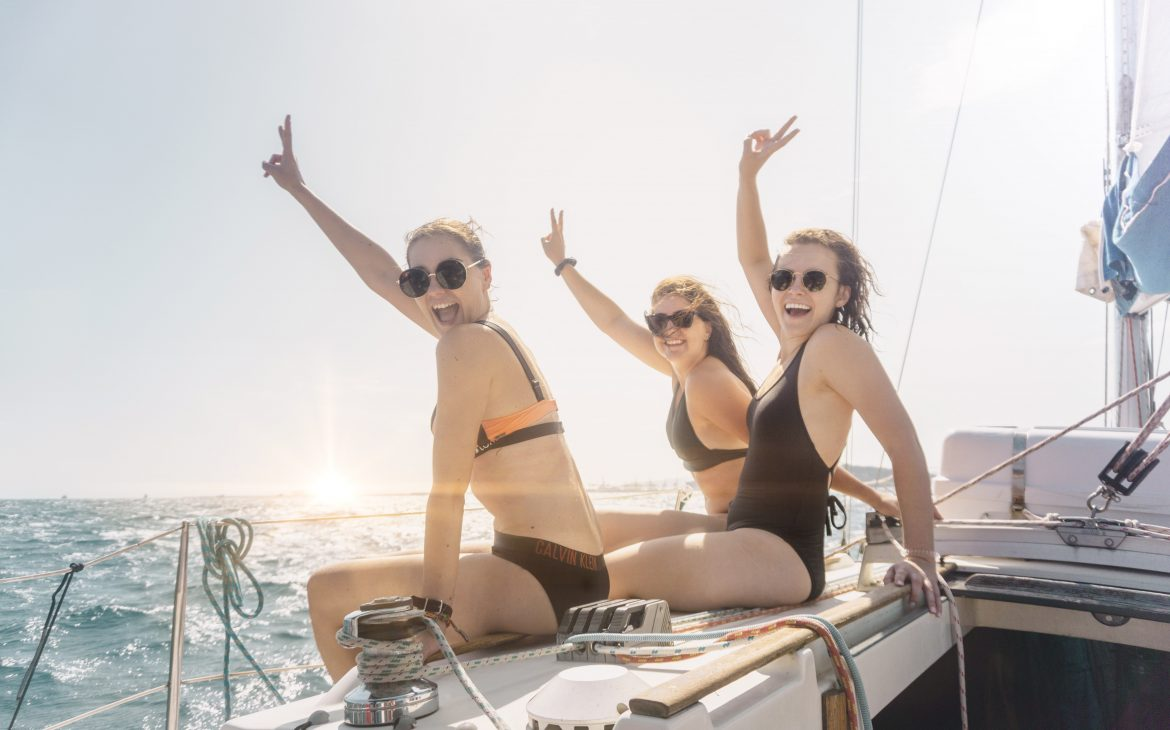 Three girls sitting on the sailing boat in Barcelona, smiling.