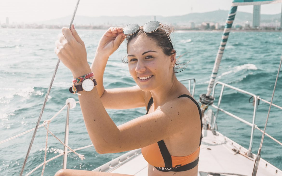 Girl sitting on the yacht in Barcelona and smiling, with the Daniel Wellington watch on her wrist.